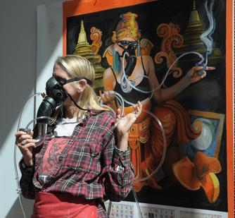 Johanna Poethig models a futuristic device; her painting shows the same device being merged with a futuristic religious culture in the form of the Hindu God Ganesh.