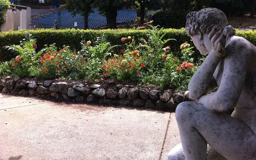 A sculpture admires a nearby flower bed