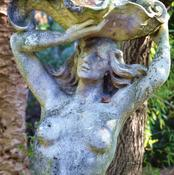 The mermaid statue in the pond along the walkway.
